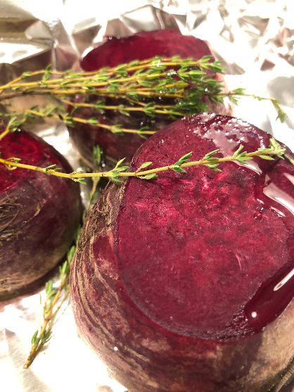 This is a photo of 3 roasted beets trimmed and drizzled with oil. Foil as the background and springs of thyme on top.