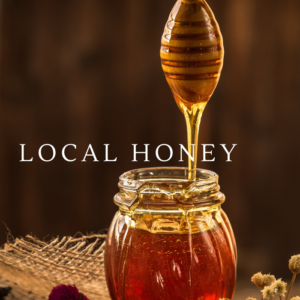 This is a jar of honey with a honey spoon drizzling into the jar. The words LOCAL HONEY is written across the front in WHITE CAPITAL LETTERS