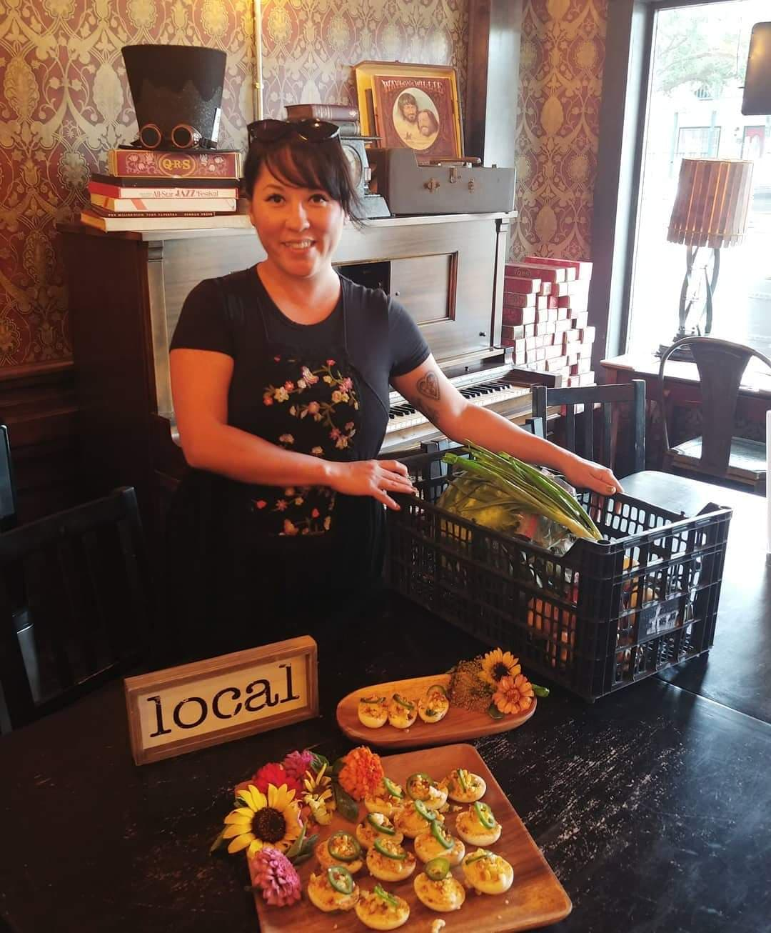 This is an image of Elyssa, Tomball Volunteer. She is in front of a piano, with deviled eggs on a platter and a farm box full of vegetables.