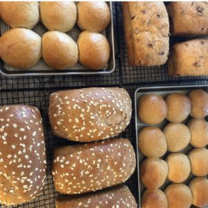 This is a photo of bread sectioned into 4 quadrant. Two of the quadrants are loaves of bread and (2) are burger buns.